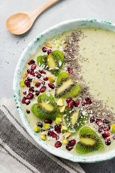 Ciotola di frullati di banana kiwi con farina d'avena, pistacchi, semi di melograno e chia su sfondo grigio chiaro di pietra