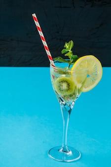 Cocktail di kiwi guarnito con limone e menta in un bicchiere su un tovagliolo contro una superficie blu
