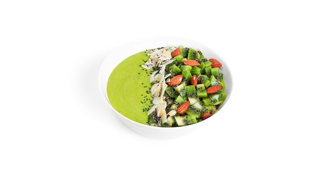 Dessert di kiwi con frutta, mandorle e semi di chia isolati su sfondo bianco. ciotola per frullato verde con frutta. foto di alta qualità