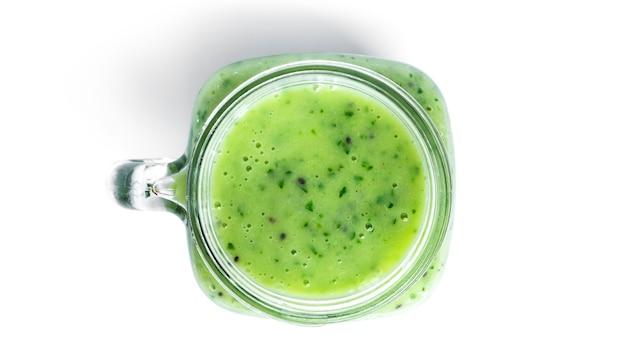 Frullato di kiwi e spinaci isolato su bianco. barattolo di vetro con frullato verde.
