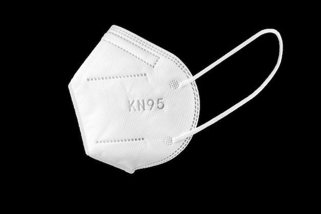 Kn95 maschera facciale isolata su sfondo nero. dispositivi di protezione individuale contro il coronavirus covid-19
