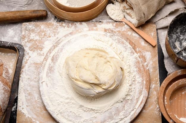 L'impasto impastato di farina di grano bianco si trova su una tavola di legno rotonda, un secchio di metallo e un mattarello di legno, vista dall'alto