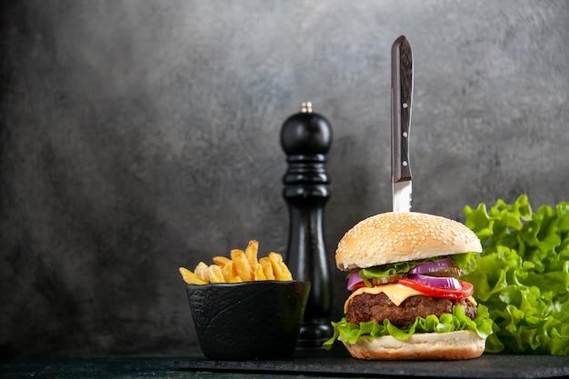 Coltello in un delizioso sandwich di carne e patatine verdi sul lato sinistro su vassoio nero su superficie grigia