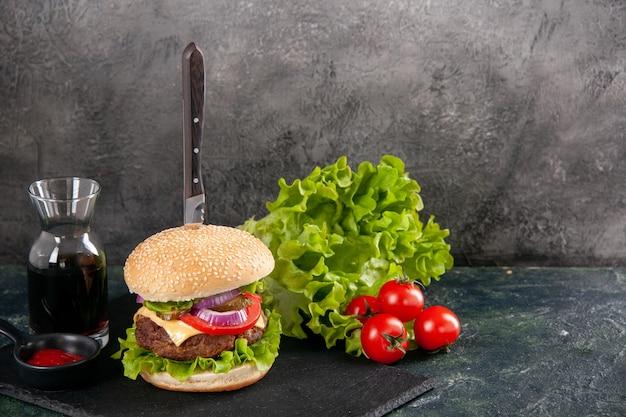 Coltello in delizioso panino di carne e pepe verde su vassoio nero salsa ketchup pomodori con gambo sul lato destro su superficie grigia