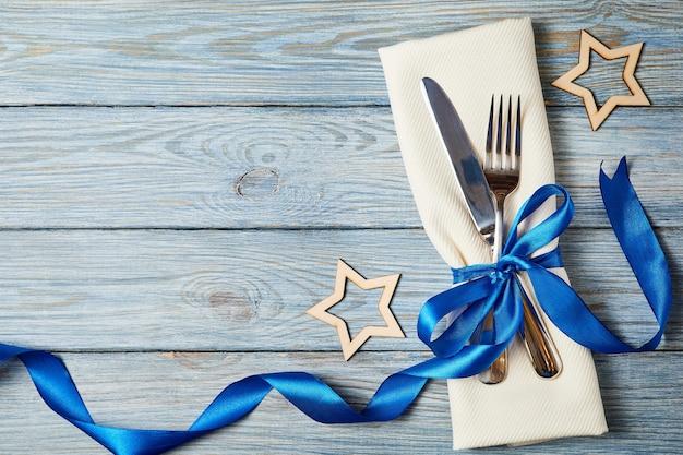 Coltello e forchetta sul tovagliolo legato con nastro blu su sfondo di legno decorato con stelle