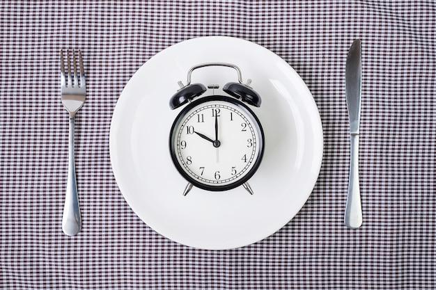 Coltello e forchetta con sveglia sul piatto bianco su sfondo tovaglia.