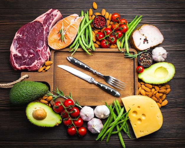 Coltello e forchetta su tagliere di legno e ingredienti chetogenici a basso contenuto di carboidrati per un'alimentazione sana e perdita di peso, vista dall'alto. alimenti cheto: carne, pesce, avocado, formaggio, verdure, noci