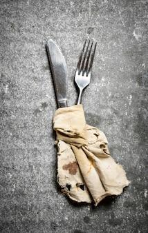 Coltello e forchetta avvolti in un vecchio panno. su uno sfondo di pietra.