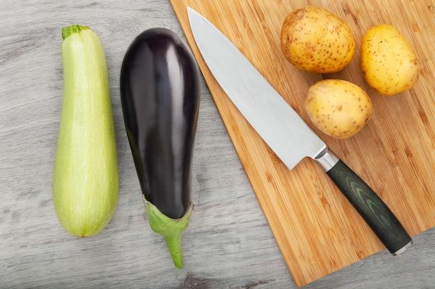 Coltello e melanzane fresche, patate e zucchine sul tagliere