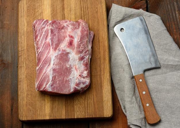 Coltello e filetto di maiale crudo su un tagliere di legno