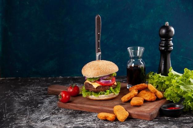 Coltello in gustoso panino di carne e pepite di pollo pomodori con gambo pepe su tavola di legno salsa ketchup sul lato sinistro su superficie blu scuro