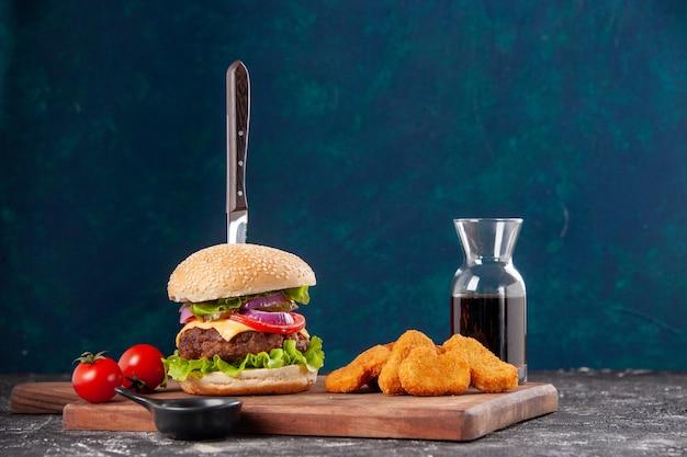 Coltello in gustoso sandwich di carne e pepite di pollo pomodori con gambo su tavola di legno salsa ketchup su superficie blu scuro dark