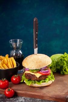 Coltello in gustosa carne con salsa di ketchup patatine fritte su tavola di legno e pomodori con gambo su superficie blu scuro dark