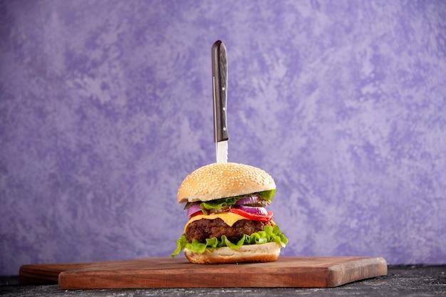 Coltello in gustoso panino di carne su tagliere di legno su superficie di ghiaccio isolata con spazio libero free