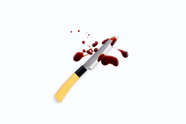 Coltello con sangue su superficie bianca.