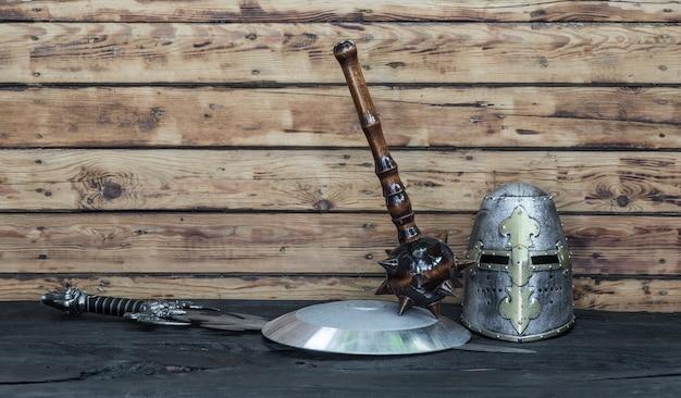 Scudo cavaliere e spada su sfondo di legno