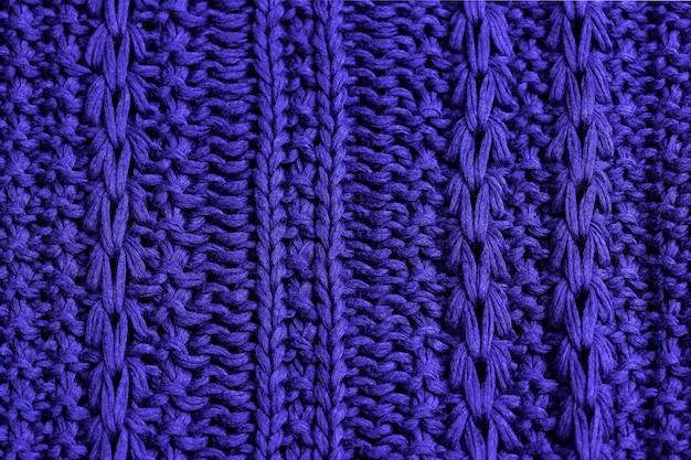 Trama a maglia di tessuto a maglia di cotone viola con motivo a cavi come sfondo.