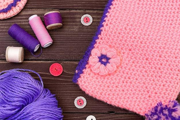 Berretto bambino lavorato a maglia e filato di pantofole per maglieria su tavola di legno accessori per il cucito