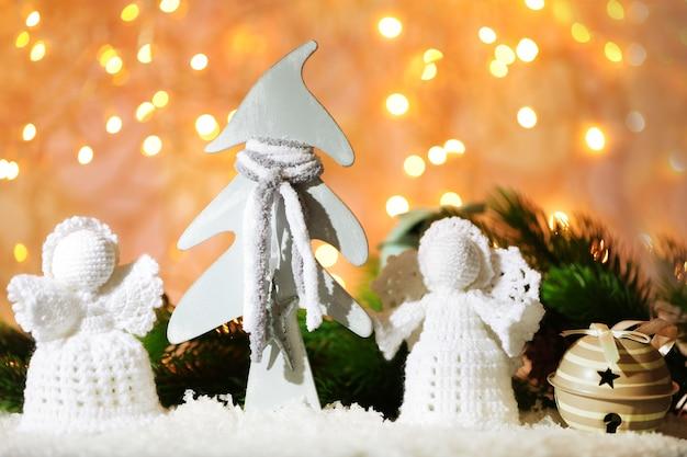 Angeli di natale lavorati a maglia e decorazioni natalizie sulla parete luminosa