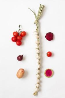 Aglio lavorato a maglia, ravanello a fettine, barbabietole a fettine, pomodori rossi e patate su fondo bianco