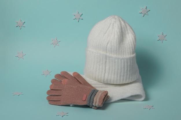 Guanti, cappello e sciarpa lavorati a maglia con fiocchi di neve. accessori invernali alla moda.
