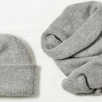 Cappello e sciarpa grigi tricottati su fondo di legno bianco. vestiti caldi alla moda per ragazza o donna.