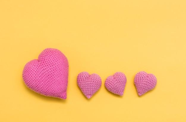 Cuori rosa grandi e piccoli lavorati a maglia su sfondo giallo. copia spazio