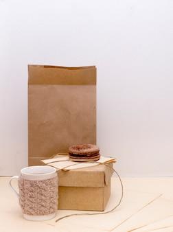 Tazza lavorata a maglia, scatola di cartone e amaretto al cioccolato su sacchetto di carta