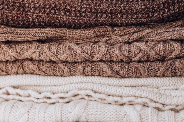 Il mucchio lavorato a maglia della struttura dei vestiti dei toni marroni di usura.
