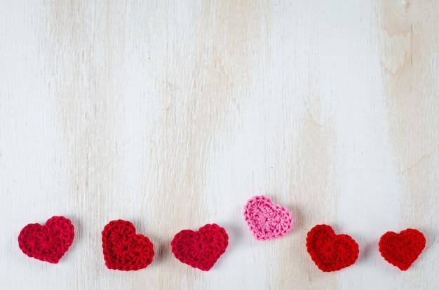 Cuori rossi lavorati a maglia su un fondo di legno bianco