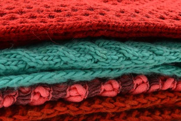 Sciarpe lavorate a maglia rosse, arancioni, verdi. collezione di vestiti di lana.