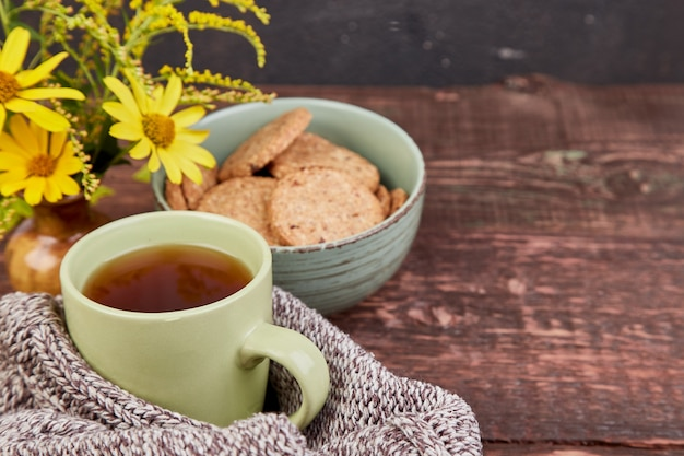 Sciarpa lavorata a maglia con calda tazza di tè