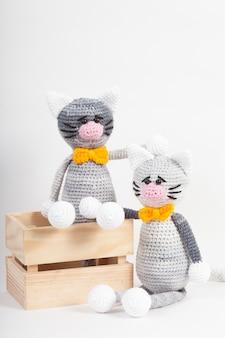 Piccolo gatto tricottato su un bianco. giocattolo fatto a mano a maglia. amigurumi