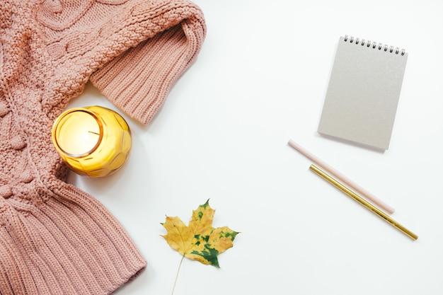 Maglione lavorato a maglia, notebook, congedo autunnale, candela su sfondo bianco. composizione autunnale. appartamento laico, vista dall'alto, copia dello spazio