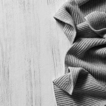 Maglione lavorato a maglia sulla vecchia tavola di legno d'epoca