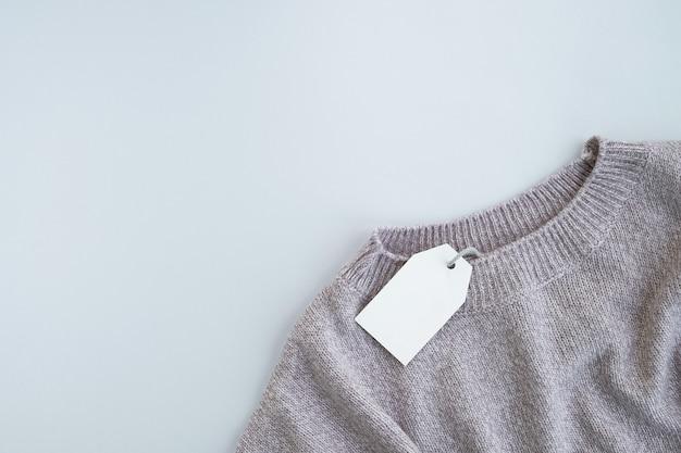 Maglione lavorato a maglia con etichetta vuota sulla superficie grigia. saldi autunnali o invernali