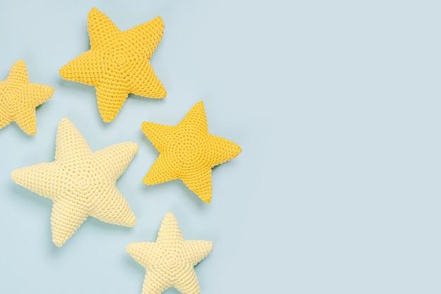 Stelle gialle tricottate del giocattolo su fondo blu. roba e accessori per bambini. disposizione piatta, vista dall'alto