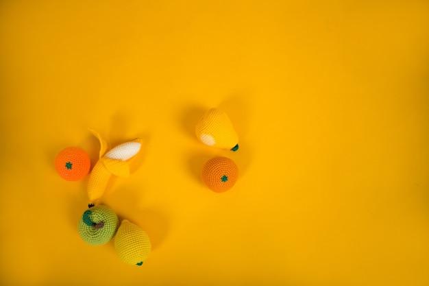 I giocattoli a maglia giacciono su uno sfondo giallo