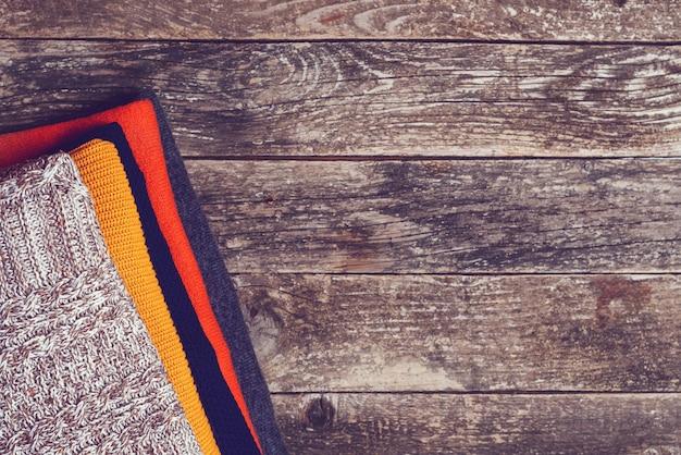 Vestiti caldi a maglia su fondo di legno, vista dall'alto, copia dello spazio. abiti color lana, stile vintage. pila di maglieria di lana piegata. moda autunno inverno stagione, concetto di guardaroba.