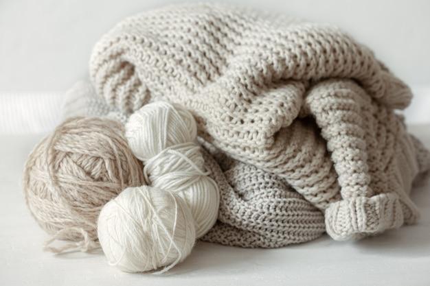 Maglioni caldi lavorati a maglia in colori pastello e matasse di filo da vicino.