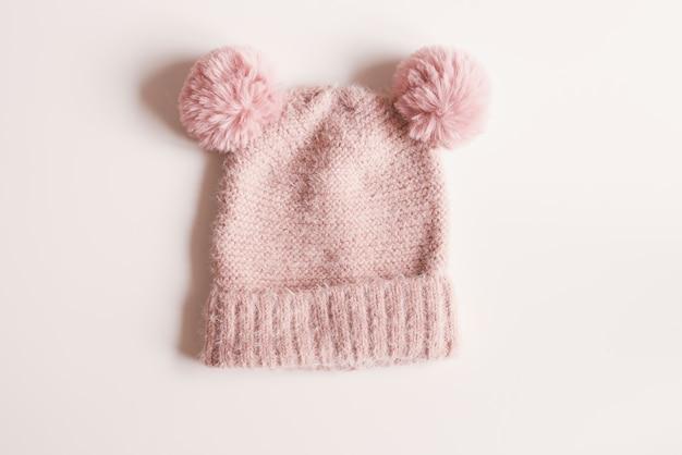 Cappello di lana lavorato a maglia di colore rosa con pompon su sfondo bianco. abbigliamento caldo autunnale o invernale