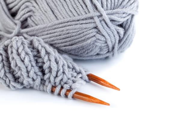 Ferri da maglia e fili di lana grigi e gialli isolati