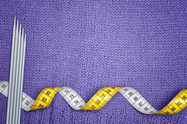 Ferri da maglia e un centimetro giallo su un tessuto a maglia lilla