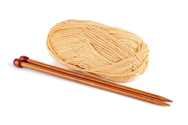 Ferri da maglia e fili di lana gialli isolati