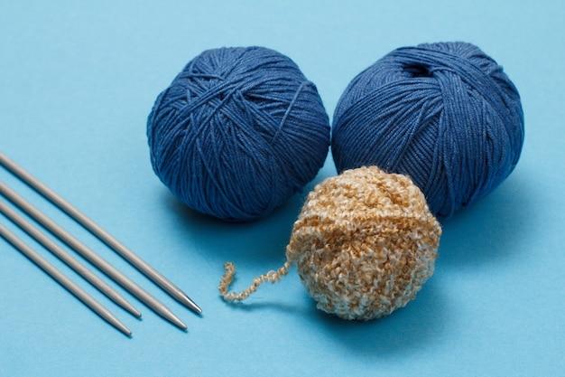 Palline di filato per maglieria e ferri da maglia in metallo su sfondo blu. concetto di maglieria. vista dall'alto.