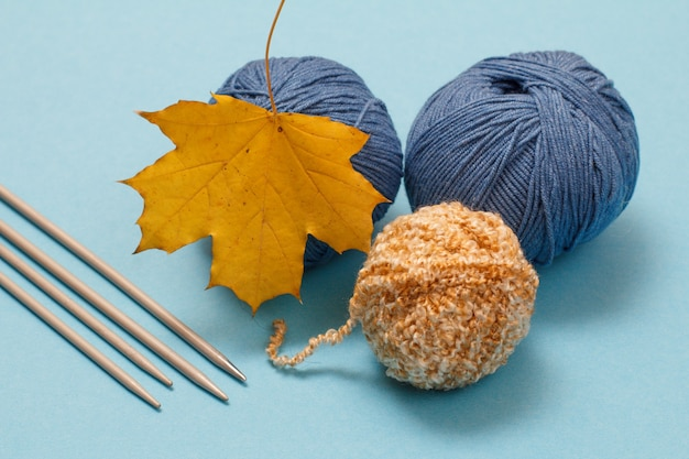 Palline di filato per maglieria, ferri da maglia in metallo e foglia d'acero secca su sfondo blu. concetto di maglieria.