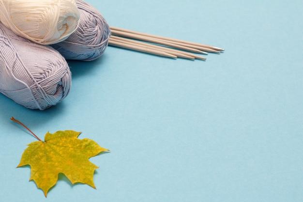 Palline di filato per maglieria, ferri da maglia in metallo e foglia d'acero su sfondo blu. concetto di maglieria. vista dall'alto.