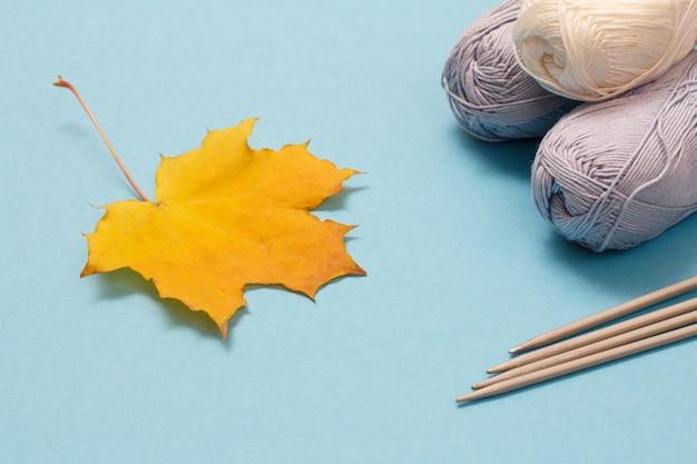 Palline di filato per maglieria, ferri da maglia in metallo e foglia d'acero su sfondo blu. concetto di maglieria.