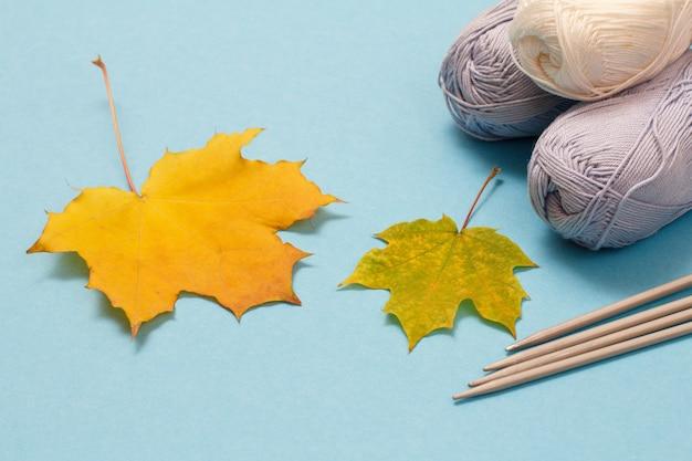 Palline di filato per maglieria, ferri da maglia in metallo e foglie di acero su sfondo blu. concetto di maglieria.