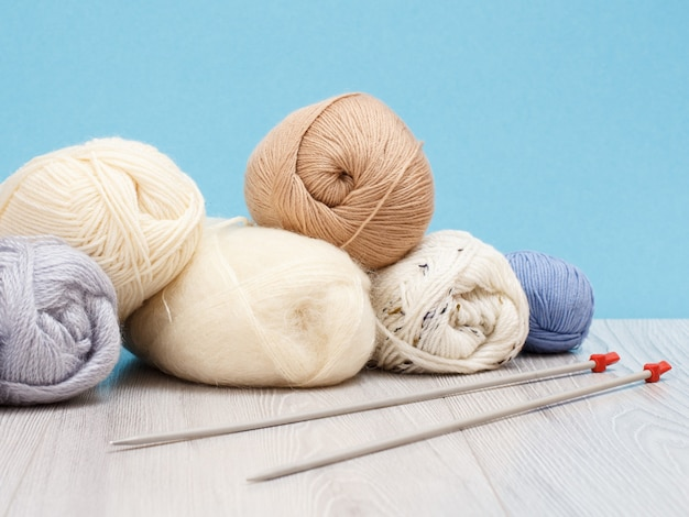 Palline di filato per maglieria e ferri da maglia in metallo su tavole di legno e sfondo blu. concetto di maglieria.